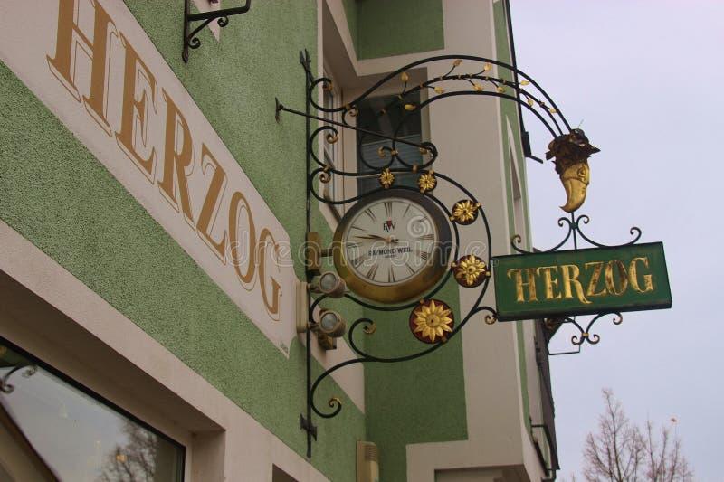 Muestra histórica del gremio del labrado-hierro delante de una tienda del reloj Windischgarsten, Austria imagen de archivo