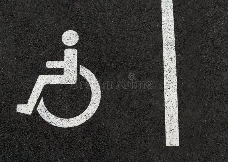 Muestra perjudicada del estacionamiento de las personas discapacitadas para la silla de rueda de coche fotografía de archivo