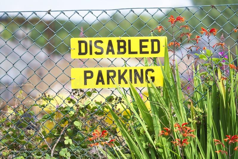Muestra que parquea discapacitada en el número de matrícula del coche en la cerca con las flores en el centro de jardín imágenes de archivo libres de regalías