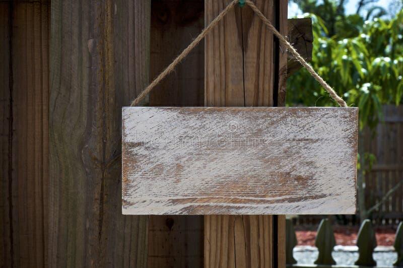 Muestra rústica en blanco que cuelga de la cerca de madera fotos de archivo libres de regalías
