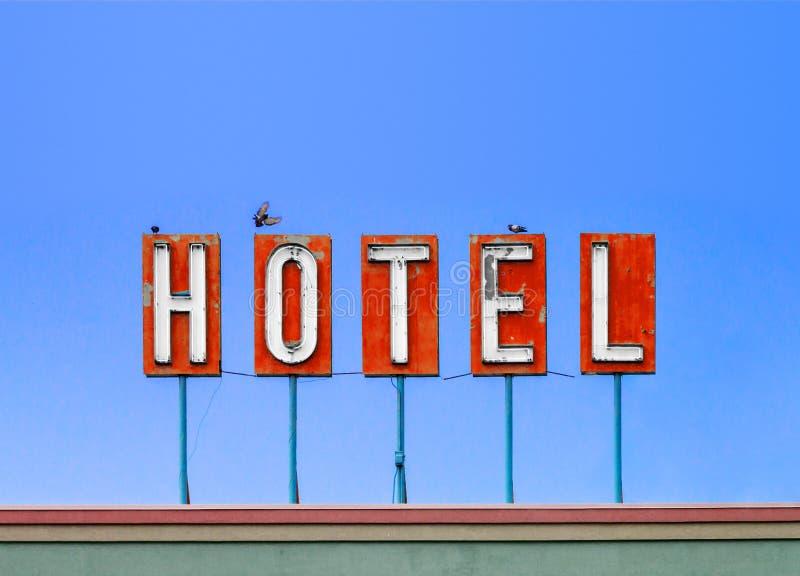 Muestra roja del hotel encima de un motel viejo sucio aislado en el cielo azul imagen de archivo