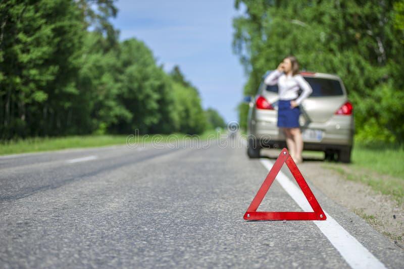 Muestra roja del triángulo en el camino y la mujer joven que piden coche como imagen de archivo libre de regalías