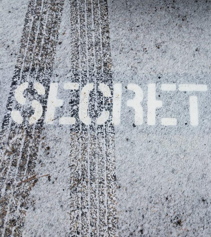 Muestra secreta en el asfalto negro con las pistas del neumático y la nieve blanca imágenes de archivo libres de regalías