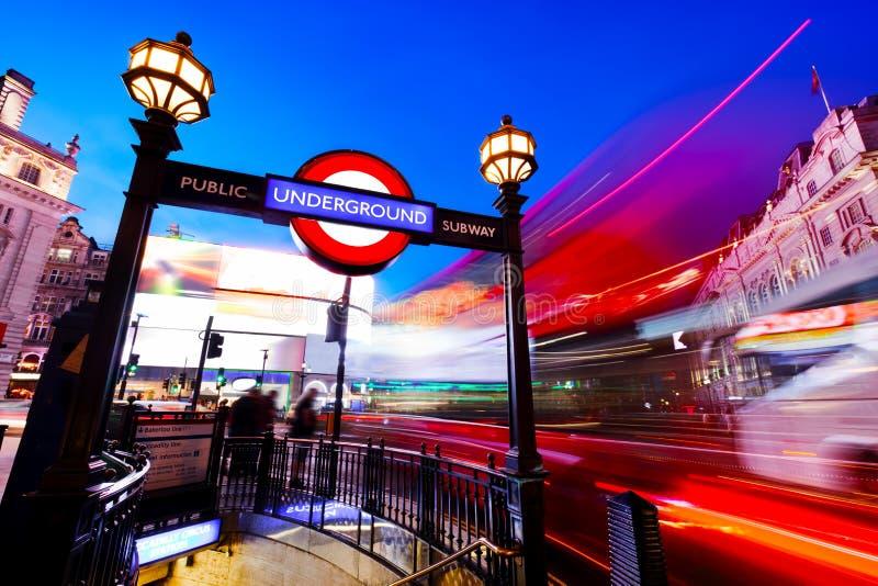 Muestra subterráneo, autobús rojo en el movimiento en el circo de Piccadilly Londres, Reino Unido en la noche fotografía de archivo