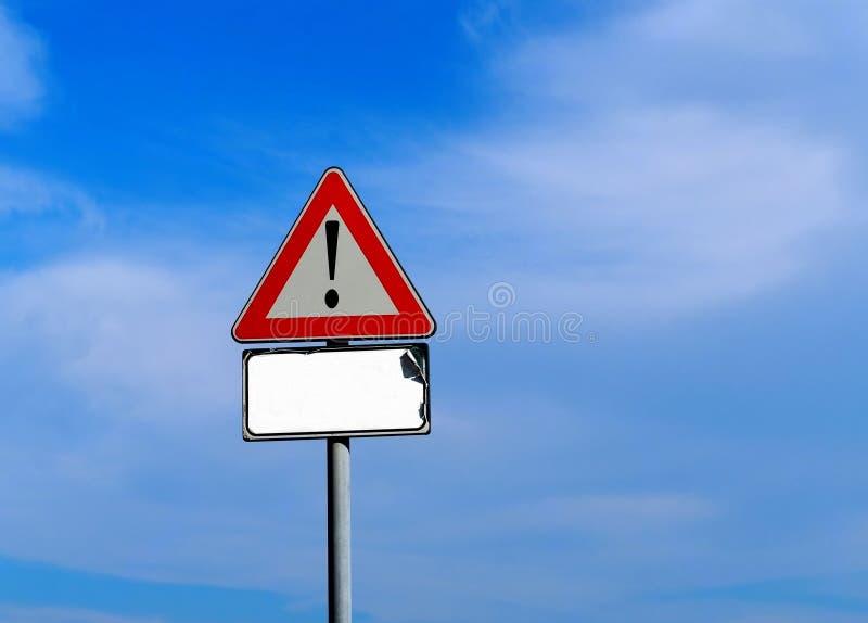 Muestra triangular amonestadora con la marca de exclamación Un poste indicador blanco gastado está abajo, sin texto fotos de archivo