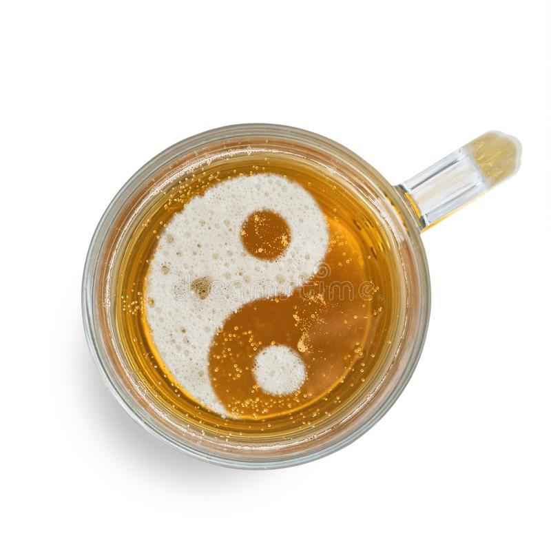 Muestra Yin-Yang en la espuma de la cerveza en el vidrio aislado en el fondo blanco Visi?n superior fotos de archivo libres de regalías