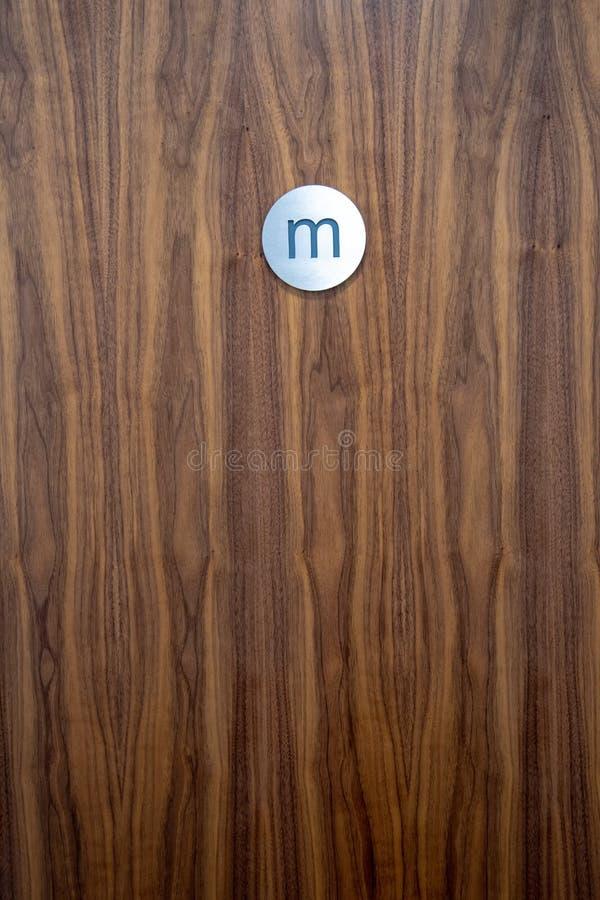 Muestras de madera del retrete de la puerta y del varón foto de archivo