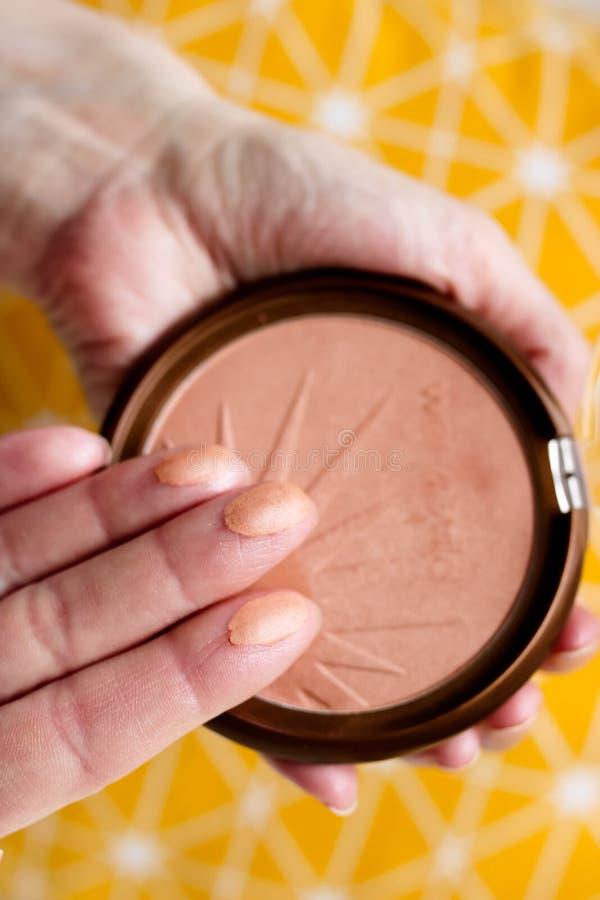 Muestras del polvo de cara en los fingeres femeninos en fondo colorido del yelow Componga el concepto fotos de archivo