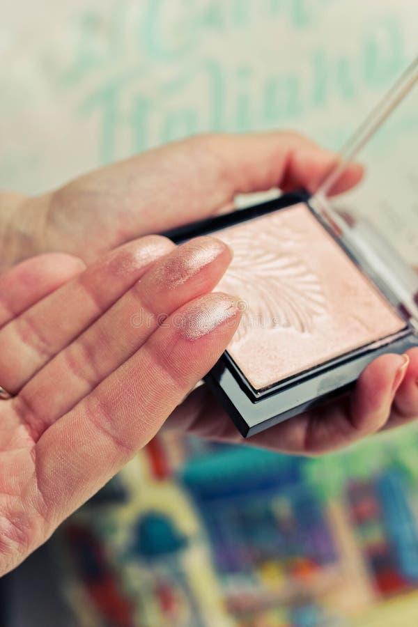 Muestras del polvo de cara en los fingeres y la paleta femeninos del polvo en fondo borroso colorido imagenes de archivo