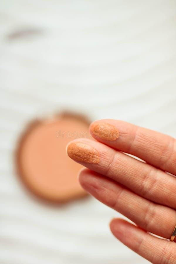 Muestras en los fingeres de la mujer Pallete del polvo de cara Fondo borroso blanco foto de archivo libre de regalías