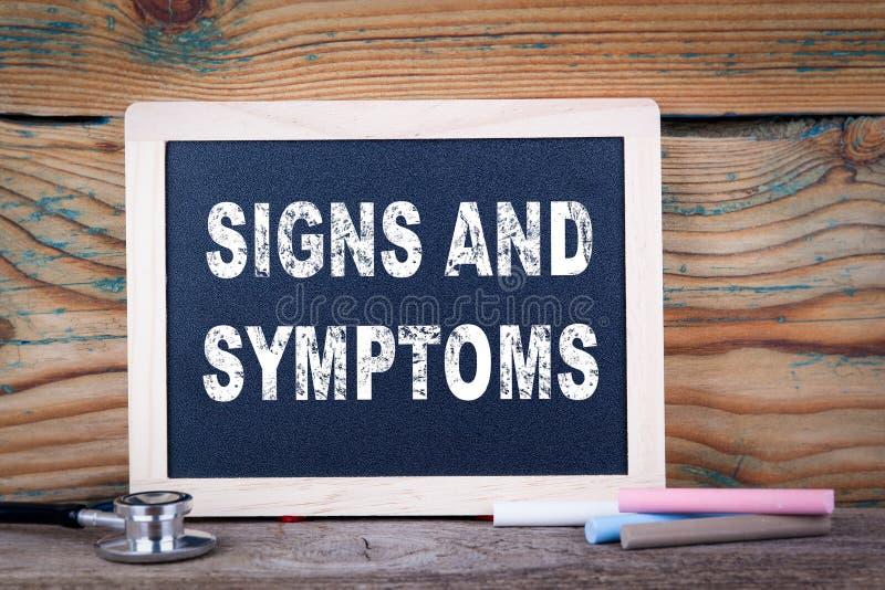 Muestras y síntomas Pizarra en un fondo de madera fotografía de archivo