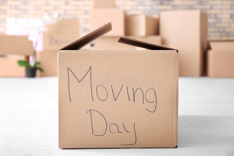 Mueva el concepto de la casa Caja del cartón en piso imagen de archivo