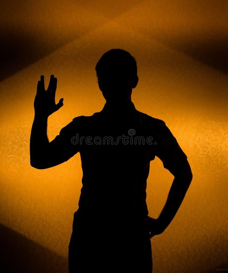 Mueva hacia atrás la silueta encendida del hombre con la mano levantada imágenes de archivo libres de regalías