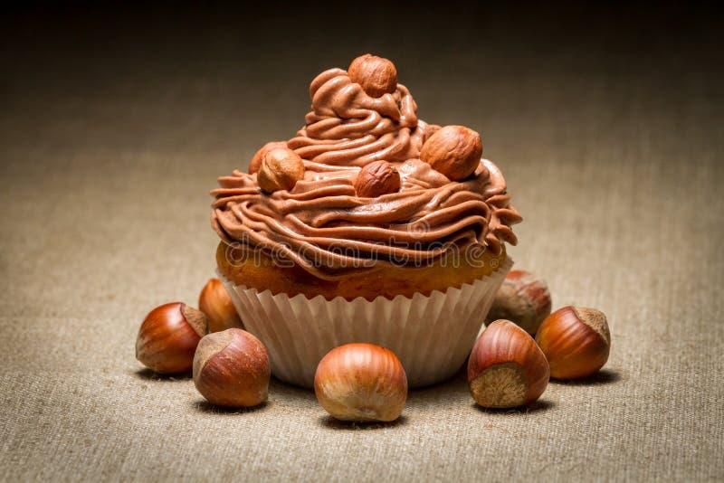 Muffin κινηματογραφήσεων σε πρώτο πλάνο με την κρέμα και τα φουντούκια σοκολάτας στοκ εικόνα