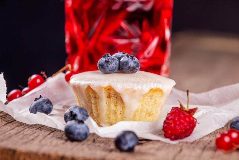 Muffin με το μπλε μούρο berries^, το σμέουρο, την κόκκινη σταφίδα και το ποτήρι compote φρούτων στοκ φωτογραφία