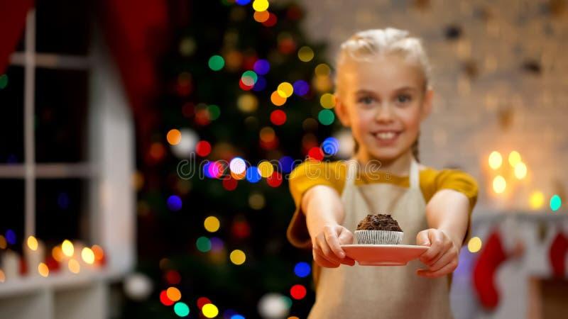 Muffin adorabile di rappresentazione della ragazza alla macchina fotografica ed a sorridere, atmosfera felice di natale fotografie stock libere da diritti