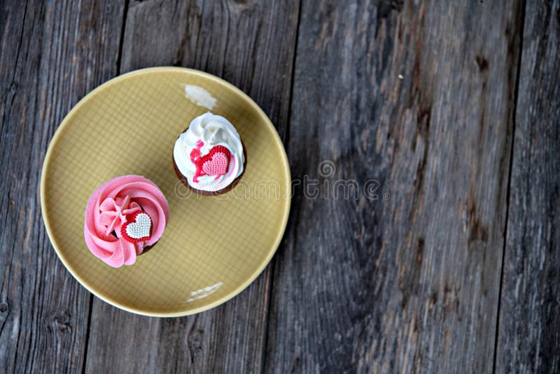 Muffin bianchi e di rosa con cuore su terra di legno immagini stock libere da diritti