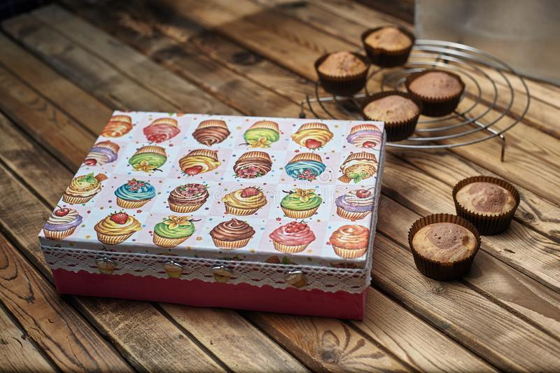 Muffin bredvid en gåvaask på en trätabell royaltyfria foton