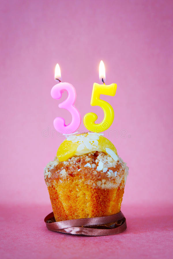 Muffin with burning birthday candles as number thirty five. On pink background royalty free stock photography