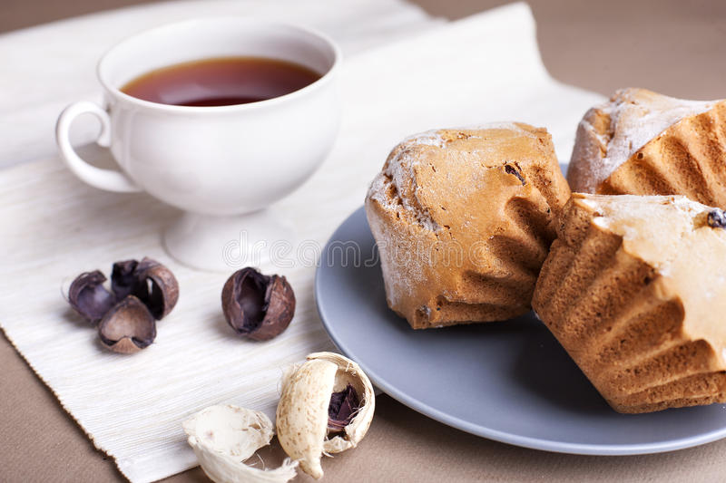 Muffin cakes and cup of tee. On a grey plate. Beige - coffee background stock images