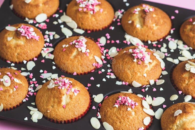 Muffin con la decorazione dell'innamorato, fondo rosa, cuore di carta con testo ti amo fotografia stock libera da diritti