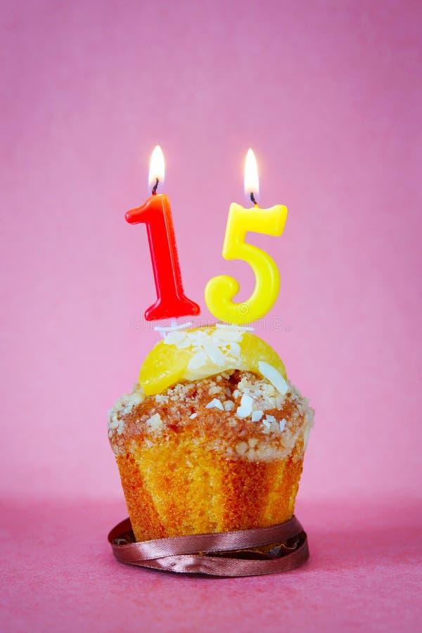 Muffin con le candele brucianti di compleanno come numero quindici fotografie stock libere da diritti