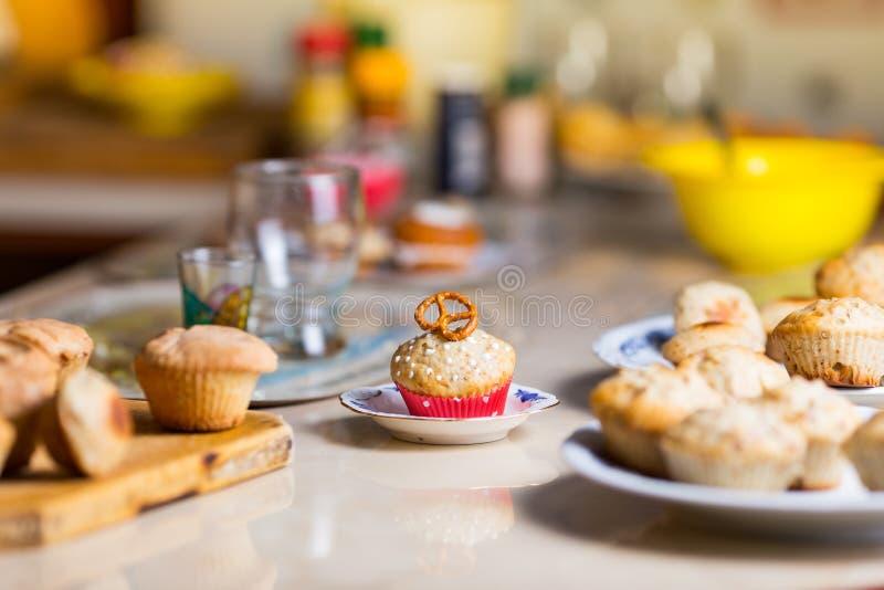 Muffin con una ciambellina salata sulla cima in un bigné rosso immagine stock