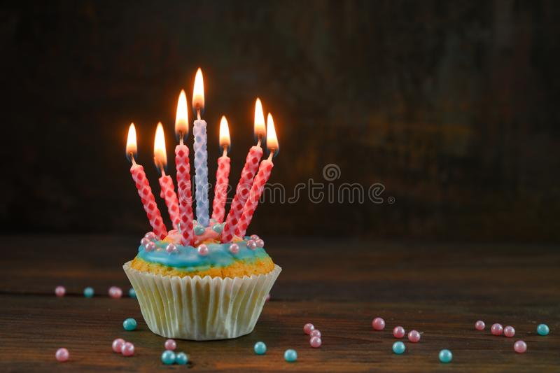 Birthday muffin or cupcake with red and blue burning candles and sugar balls on a rustic wooden board against a dark brown royalty free stock photography