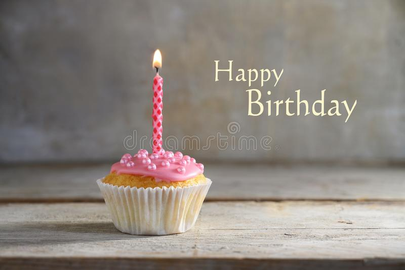 Muffin or cupcake with a pink burning candle on a wooden board against a rustic background, text Happy Birthday, greeting card stock photography