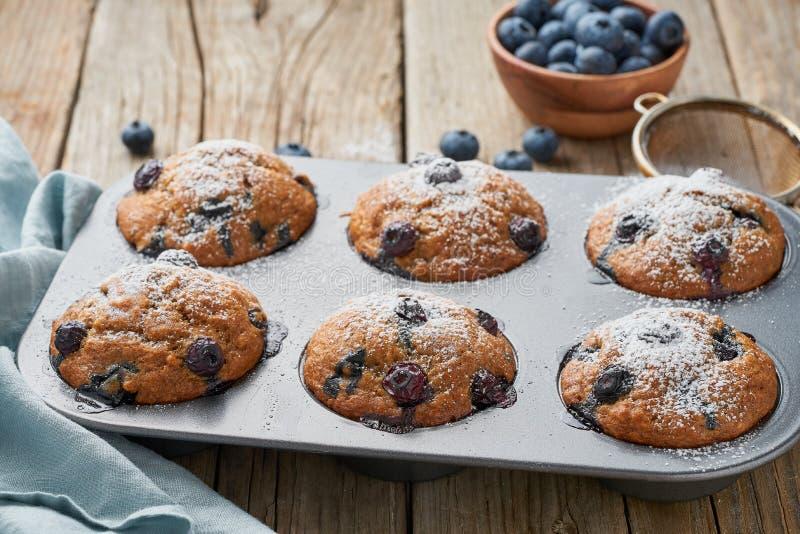 Muffin de blueberry na bandeja, vista lateral Queques com as bagas no prato de cozimento no guardanapo de linho velho, tabela de  imagem de stock royalty free