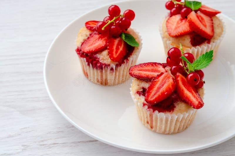 Muffin dekorerade den nya jordgubben på plattan fotografering för bildbyråer
