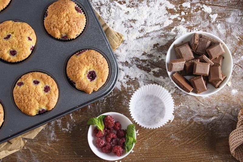 Muffin deliziosi e fragranti con i lamponi ed il cioccolato immagini stock libere da diritti