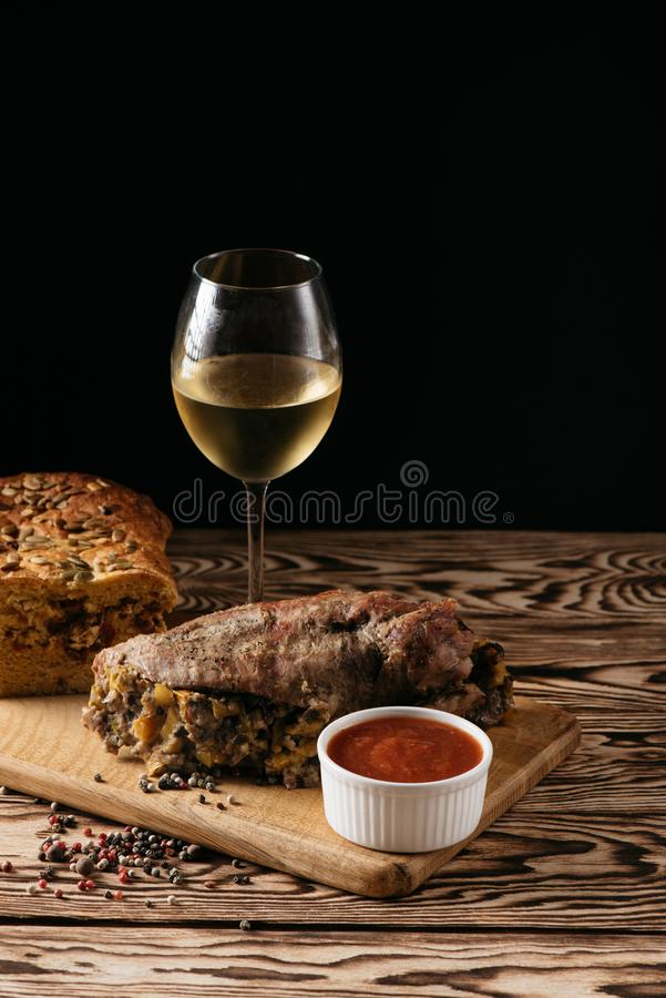 Muffin della zucca e polpettone al forno con il riempimento, con una salsa su un piatto di legno e su un vetro di vino bianco su  fotografia stock