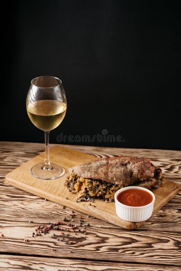 Muffin della zucca e polpettone al forno con il riempimento, con una salsa su un piatto di legno e su un vetro di vino bianco su  fotografie stock libere da diritti
