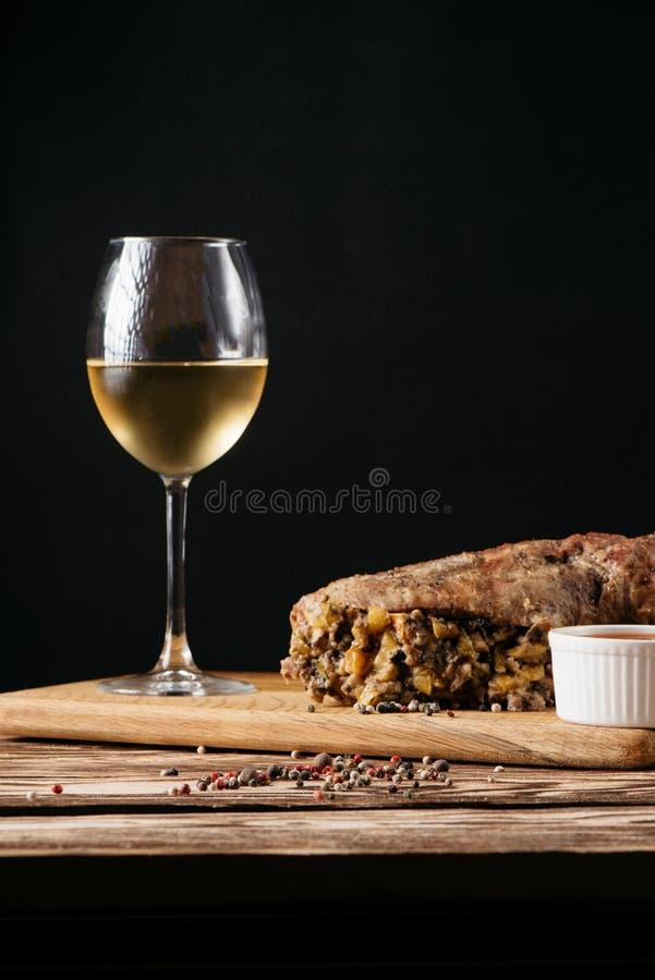 Muffin della zucca e polpettone al forno con il riempimento, con una salsa su un piatto di legno e su un vetro di vino bianco su  immagini stock