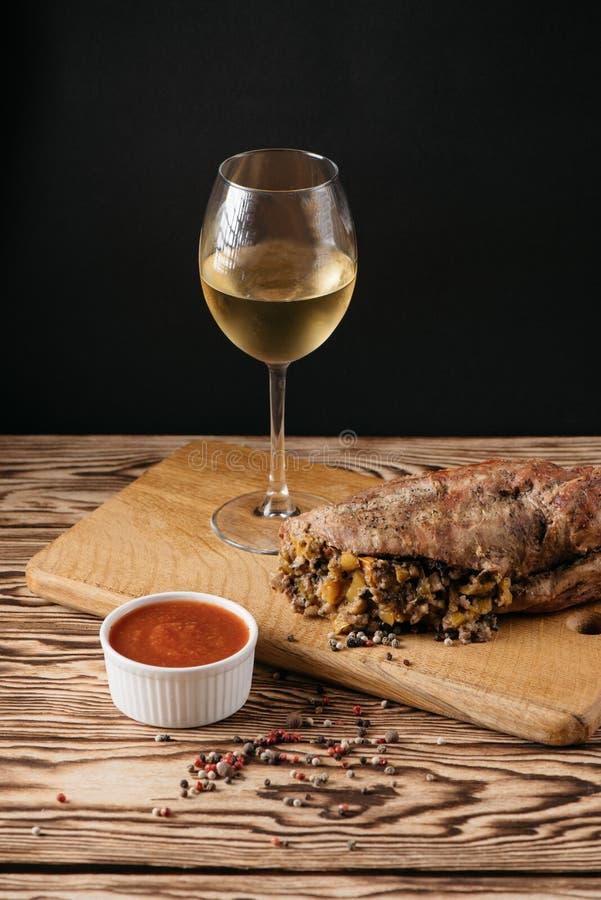Muffin della zucca e polpettone al forno con il riempimento, con una salsa su un piatto di legno e su un vetro di vino bianco su  immagini stock libere da diritti