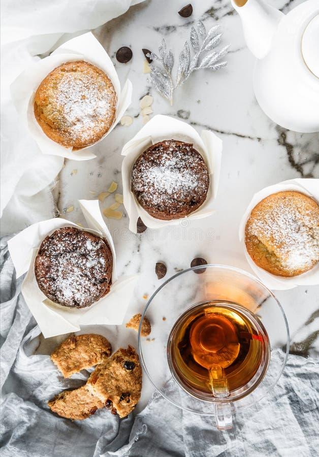 Muffin eller muffin med kakor och kopp te på ljus marmorerar bakgrund med servetten Semestra kakaberöm som är läcker royaltyfri bild