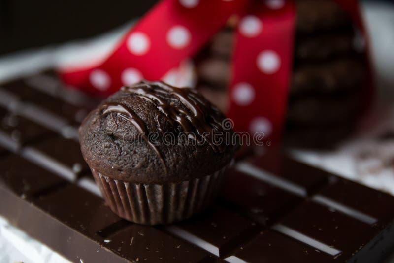 Muffin en chocoladeschilfer het koekje met chocoladereep en rode zijde buigt met witte punten stock fotografie
