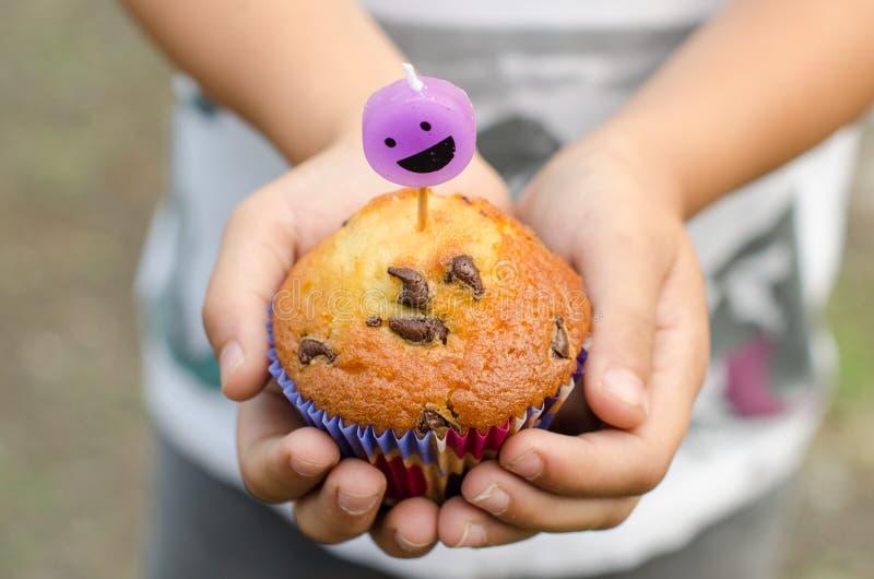 Muffin för chokladchip och smileystearinljus arkivbild