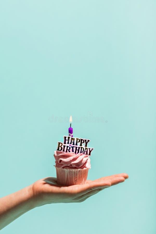 Muffin för födelsedag för hand för kvinna` s hållande med stearinljuset royaltyfri fotografi