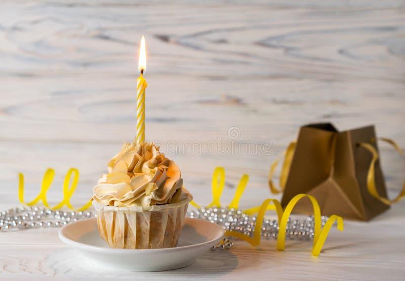 Muffin för lycklig födelsedag med den tända stearinljuset och en gåva arkivfoto