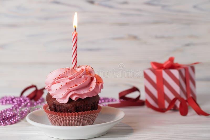Muffin för lycklig födelsedag med rosa körsbärsröd anstrykning som glaserar med den tända stearinljuset royaltyfria bilder