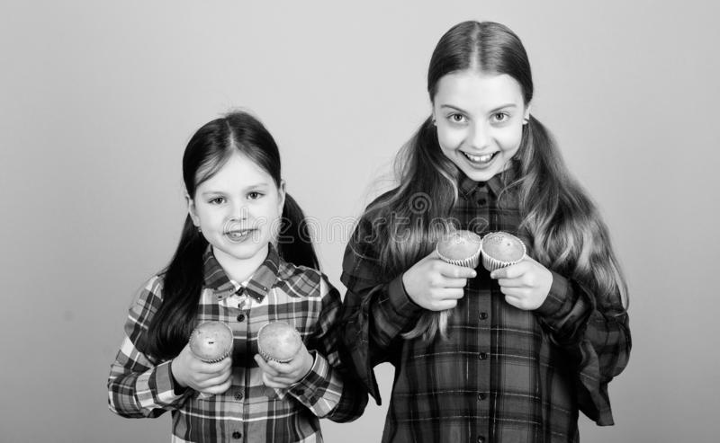 Muffin fight. Small children happy smiling with quickbread muffins. Happy little girls baking breakfast muffins at home stock photography