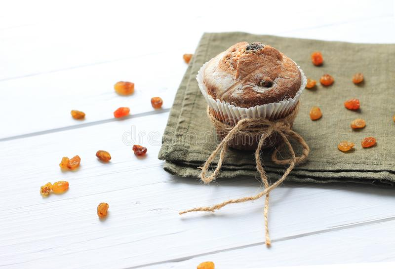 Muffin on green napkin with raisins on wooden table royalty free stock image