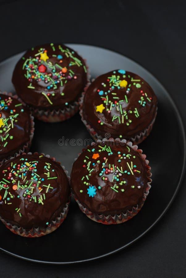 Muffin Homebaked del cioccolato per Pasqua con Conffeti colorato Fondo scuro Dessert dolce per la prima colazione fotografie stock