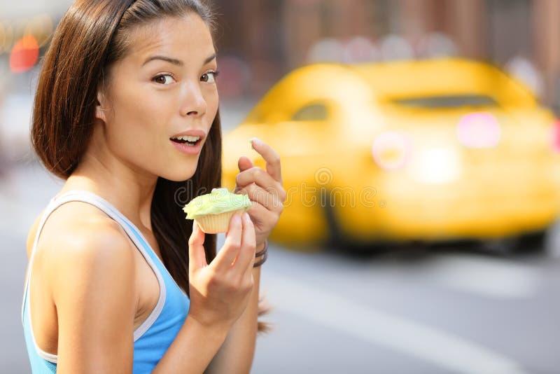Muffin - kvinna som fångas äta muffinmellanmålet arkivbild
