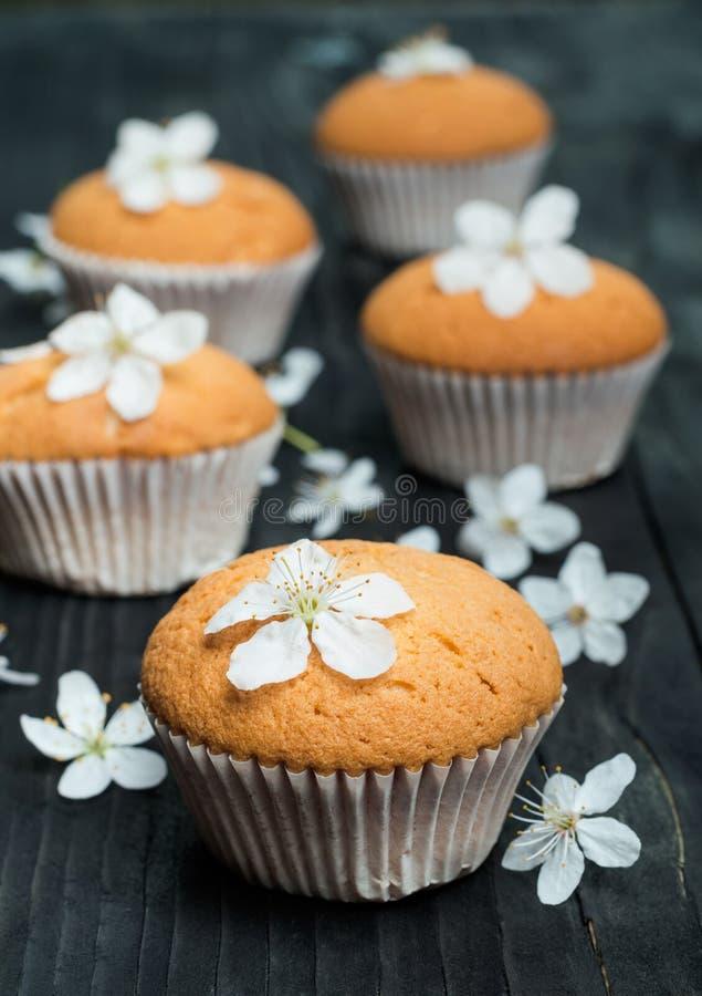 Muffin med delikata blommor på en svart lantlig tabell royaltyfria bilder