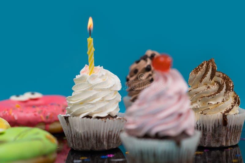 Muffin med en födelsedagstearinljusbränning royaltyfri fotografi