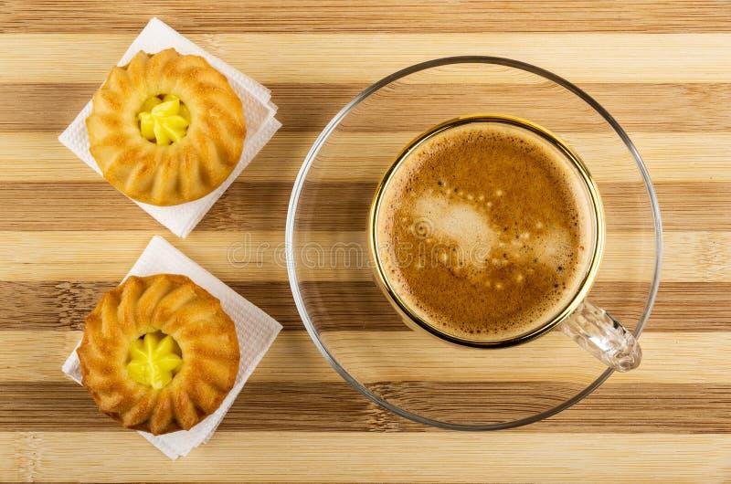 Muffin med kräm- fyllning på pappers- servetter, kaffe med mjölkar i kopp på tefatet på den randiga tabellen Top besk?dar fotografering för bildbyråer