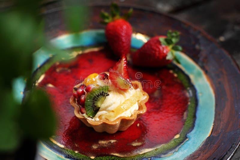 Muffin med kr?m och frukt s?t efterr?tt arkivfoton